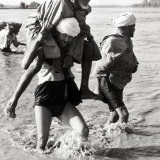 photo d'une personne aidant à traverser un fleuve à un vieilard en le portant sur ses épaules