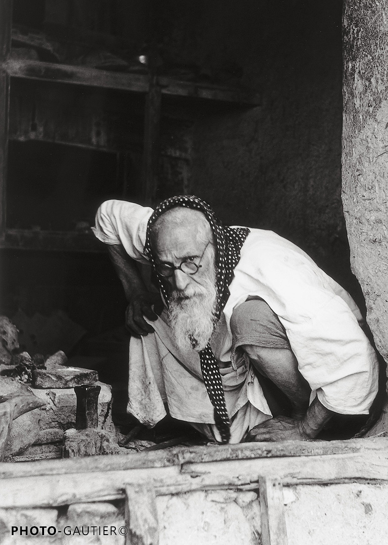 portrait communauté juive vieil homme accroupi foulard regard lunettes rondes artisan atelier hauteur