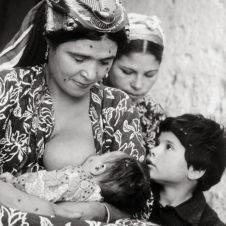 portrait d'une famille dont la mère allaite son bébé au coté du fils et de la fille