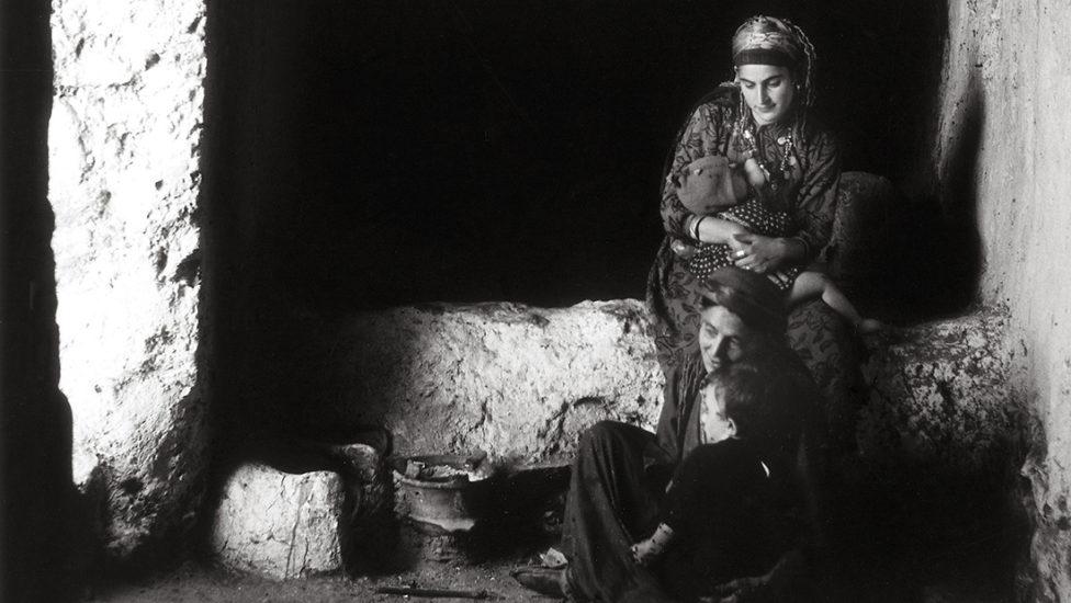 photographie d'une femme qui allaite son bébé dans une piece sombre